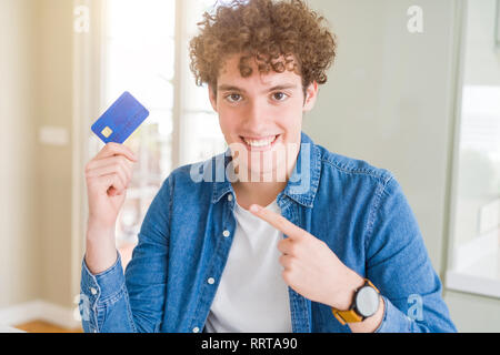 Young man holding credit card very happy pointing with hand and finger - Stock Photo