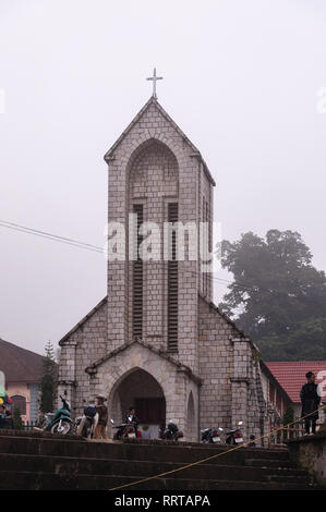 Nhà Thờ Đá Sapa or Notre Dame cathedral with local Vietnamese outside on an overcast day, Sa Pa, Vietnam - Stock Photo