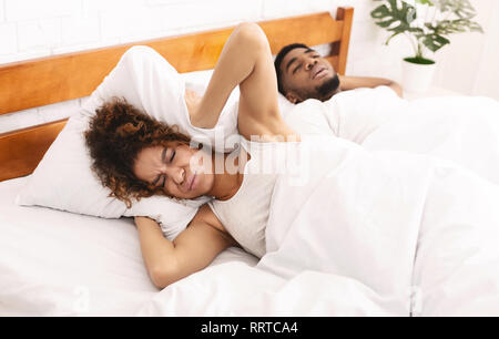 Tired and annoyed woman of her boyfriend snoring - Stock Photo
