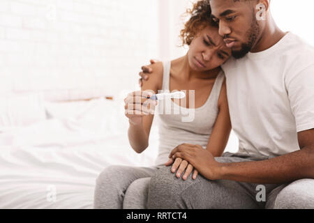 Black couple with a negative pregnancy test result - Stock Photo