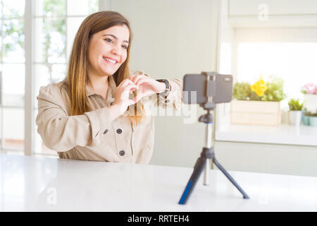 Beautiful young woman doing online video call using smartphone webcam smiling in love showing heart symbol and shape with hands. Romantic concept. - Stock Photo