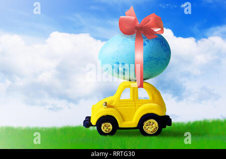 Retro toy car with Easter egg on the roof. on spring background Easter concept. Happy Easter. - Stock Photo