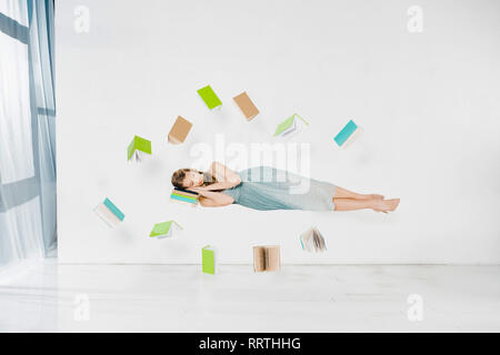 floating girl in blue dress sleeping on book in air on white background - Stock Photo