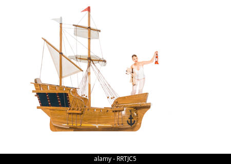 girl in pyjamas holding lantern, teddy bear and standing on floating ship model with copy space - Stock Photo
