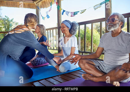 Yoga class meditating in hut during yoga retreat - Stock Photo