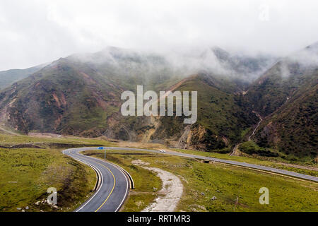 Curvy Mountain Roads in Clouds, Green Hills and White Car and New Asphalt Road. Humid Climate in Valley. - Stock Photo