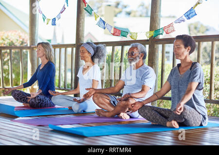 Serene people meditating in hut during yoga retreat - Stock Photo