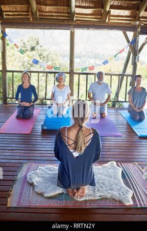 Woman leading meditation in hut during yoga retreat - Stock Photo