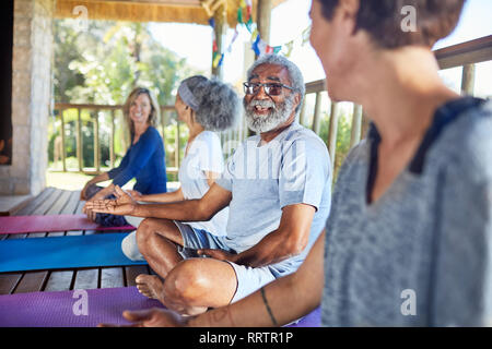 Senior man talking with woman in hut during yoga retreat - Stock Photo
