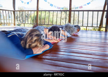 Serene people meditating in hut during yoga retreat - Stock Photo