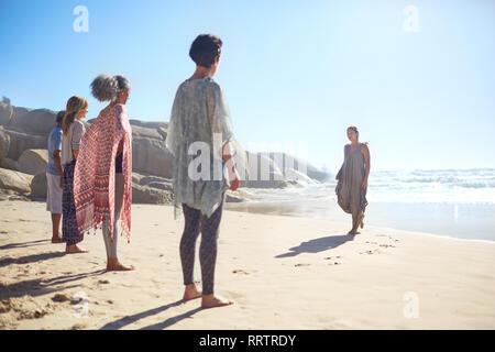 Woman leading yoga class on sunny beach during yoga retreat - Stock Photo