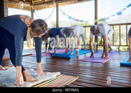 Female instructor leading yoga class in hut during yoga retreat - Stock Photo