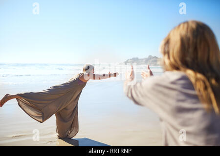 Woman practicing warrior 3 pose on sunny beach during yoga retreat - Stock Photo