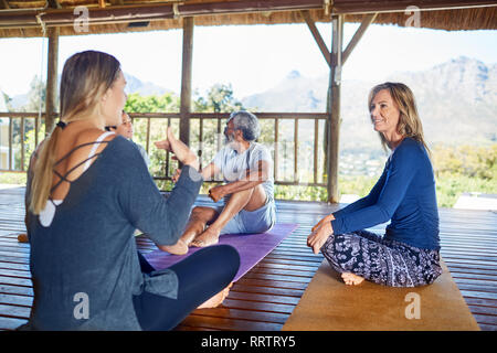 Women talking in hut during yoga retreat - Stock Photo