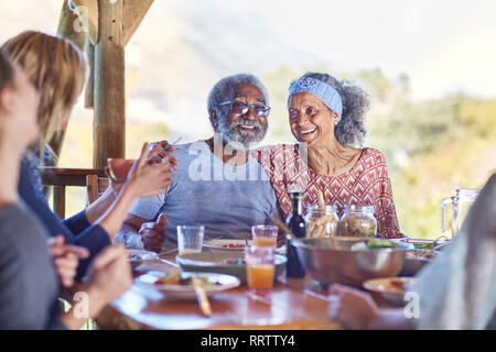 Happy senior couple enjoying healthy meal in hut during yoga retreat - Stock Photo