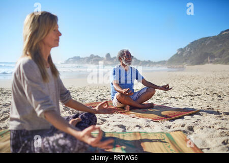 Serene people meditating on sunny beach during yoga retreat - Stock Photo