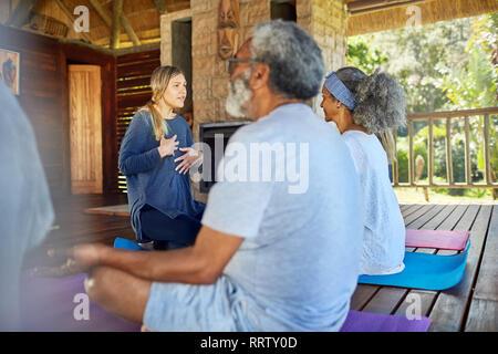 Yoga instructor leading meditation in hut during yoga retreat - Stock Photo