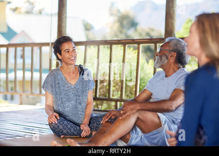 Smiling man and woman talking in hut during yoga retreat - Stock Photo