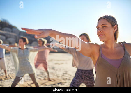 Confident woman practicing warrior 2 pose on sunny beach during yoga retreat - Stock Photo