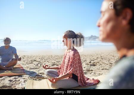 Serene senior woman meditating on sunny beach during yoga retreat - Stock Photo