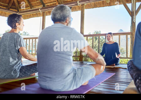Female yoga instructor leading class in hut during yoga retreat - Stock Photo