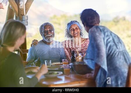 Happy senior couple enjoying breakfast on yoga retreat - Stock Photo