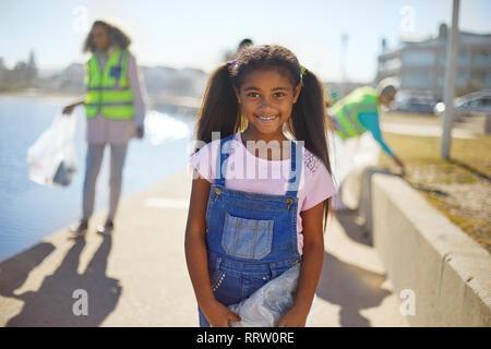 Portrait smiling girl volunteer cleaning up litter on sunny boardwalk - Stock Photo