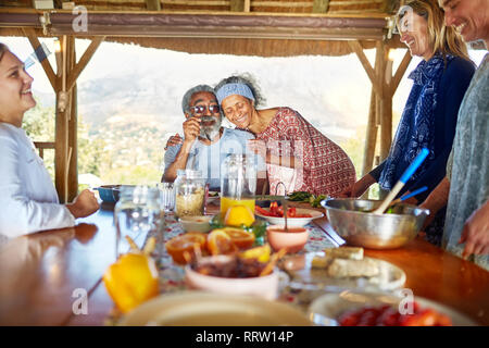 Couple hugging, enjoying healthy breakfast in hut during yoga retreat - Stock Photo