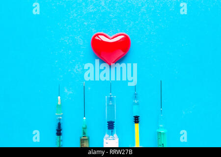 volumetric heart with syringes on a blue background. The concept of supporting patients with heart disease. - Stock Photo