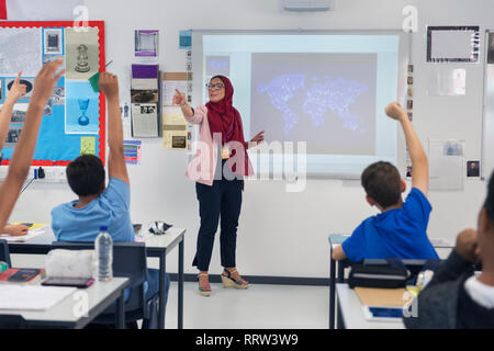 Female teacher in hijab leading lesson, calling on students in classroom - Stock Photo