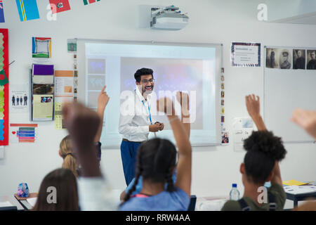 Smiling male teacher leading lesson in classroom - Stock Photo
