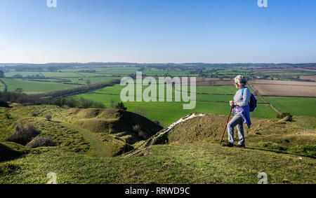 Mature female rambler admiring beautiful hilltop view from the top of White Sheet Hill in Wiltshire, UK - Stock Photo