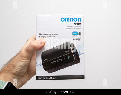 PARIS, FRANCE - OCT 30, 2018: Man hoding cardboard box of new Omron Evolv Bluetooth Wireless Upper Arm Blood Pressure Monitor against white background - Stock Photo