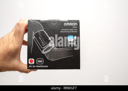 PARIS, FRANCE - OCT 30, 2018: Hand hoding cardboard box of Omron Evolv Bluetooth Wireless Upper Arm Blood Pressure Monitor against white background - Stock Photo