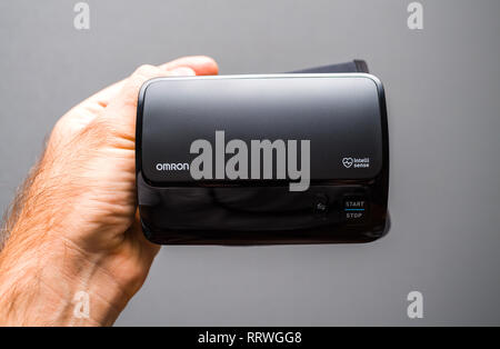 PARIS, FRANCE - OCT 30, 2018: Man holding new Omron Evolv Bluetooth Wireless Upper Arm Blood Pressure Monitor against white background - Stock Photo
