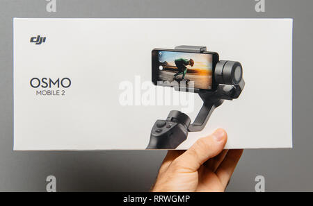 PARIS, FRANCE - NOV 22, 2018: Man hand holding against gray background new DJI Osmo Mobile 2 Smartphone Gimbal manufactured by the SZ DJI Technology Co., Ltd company - Stock Photo