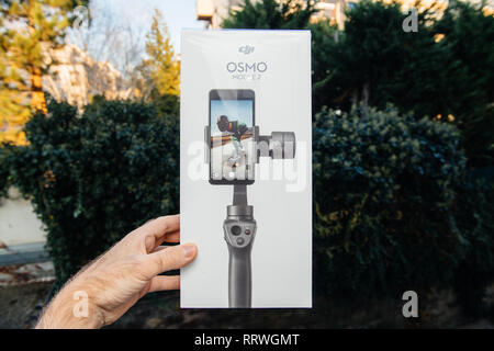 PARIS, FRANCE - NOV 22, 2018: Man hand holding in outdoor background new DJI Osmo Mobile 2 Smartphone Gimbal manufactured by the SZ DJI Technology Co., Ltd company horizontal - Stock Photo