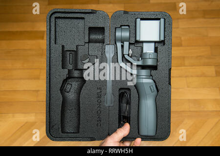 PARIS, FRANCE - NOV 22, 2018: Man unboxing new DJI Osmo Mobile 2 Smartphone Gimbal manufactured by the SZ DJI Technology Co., Ltd company from the foam packaging floor background - Stock Photo