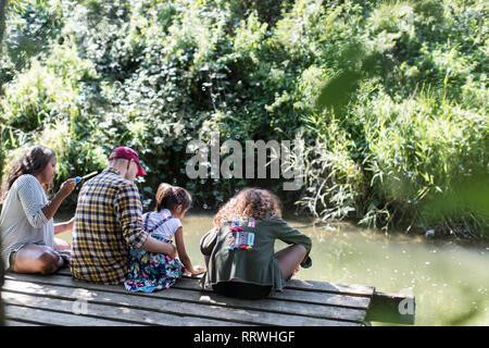 Family relaxing on dock in woods - Stock Photo