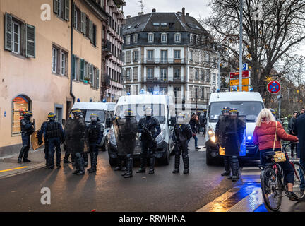 STRASBOURG, FRANCE - DEC 8, 2018: Front view of police officers securing the zone in frong of the Yellow vests movement protesters  Stock Photo