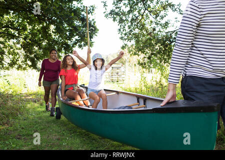 Excited family carrying canoe in woods - Stock Photo