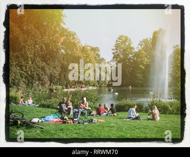 STRASBOURG, FRANCE - SEP 24, 2017: Crowd of people enjoying the sun on an early autumn day in Strasbourg Orangerie public park on the border of a lake with a fountain vintage film frame - Stock Photo