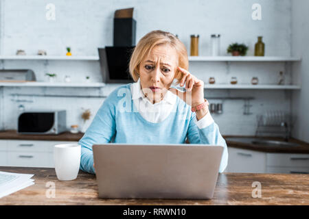 shocked senior woman touching face, using laptop and having video chat in kitchen
