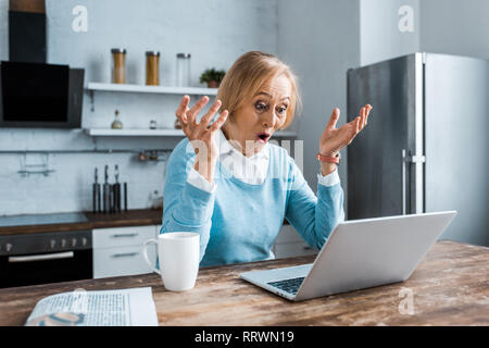 surprised senior woman gesturing with hands, using laptop and having video chat in kitchen