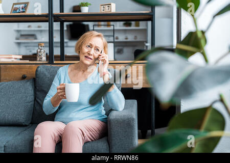 confused senior woman with cup of coffee sitting on couch and talking on smartphone in living room - Stock Photo
