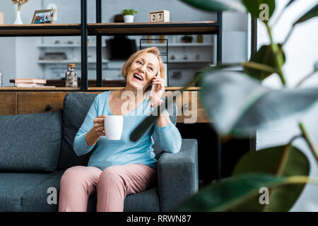 laughing senior woman with cup of coffee sitting on couch and talking on smartphone in living room