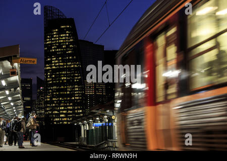 Commuters wait on the platform for the arrival of their commuter train, Courbevoie, France - Stock Photo