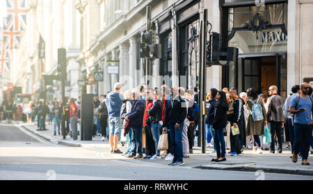 LONDON, UNITED KINGDOM - MAY 18, 2018: Pedestrians waiting to cross the Regent Street in London - long telephoto view - Stock Photo