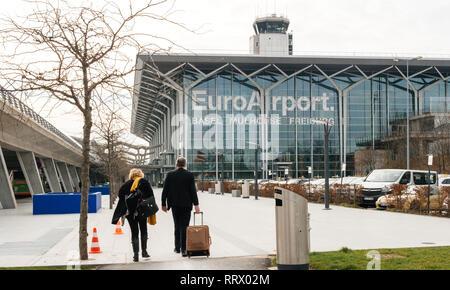BASEL, SWITZERLAND - MAR 22, 2018: Commuters couple walking toward EuroAirport Basel Mulhouse Freiburg glass facade - wide angle view - Stock Photo