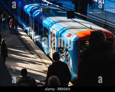 HAMBURG, GERMANY - MAR 20, 2018: Blue train in Hamburg Hauptbahnhof  with commuters on a busy day - Stock Photo